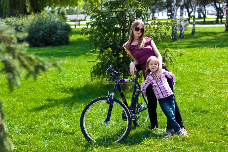lycklig ung moder med henne dotterridningbicyc fotografering för bildbyråer
