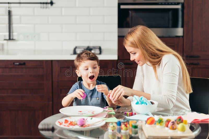 Lycklig ung moder och son som tillsammans äter hemlagade påskägg royaltyfri fotografi
