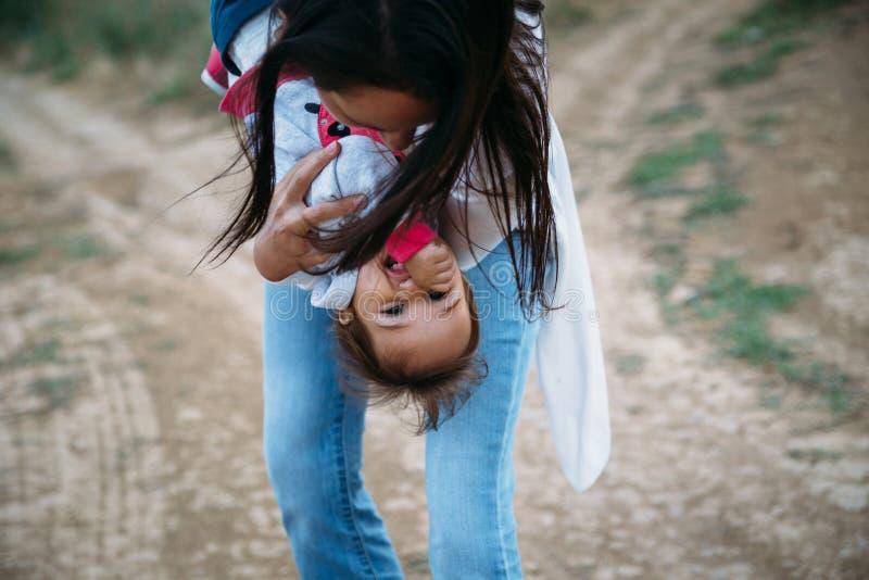 Lycklig ung moder som spelar med en liten dotter som rymmer den lilla flickan uppochnervänd, utomhus bakgrund arkivfoto