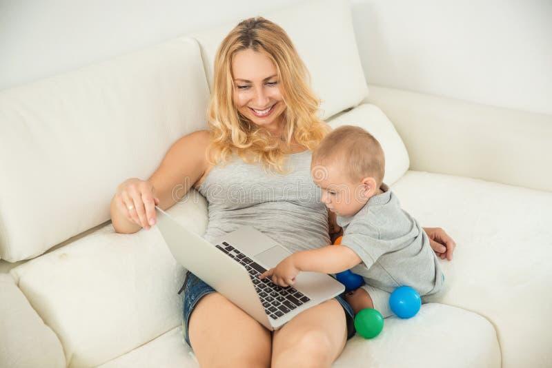 Lycklig ung moder som spelar med hennes son soffan royaltyfri foto