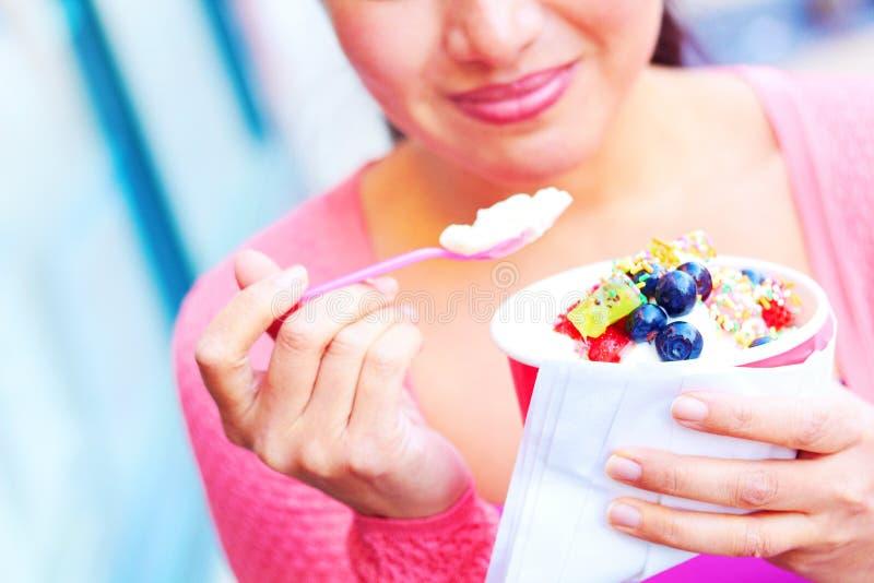 Lycklig ung nätt kvinnlig för blandat lopp som äter den fryste yoghurten royaltyfri fotografi
