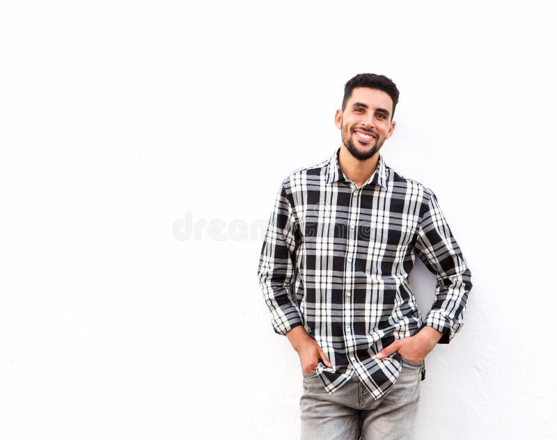 Lycklig ung norr afrikansk man som ler mot vit bakgrund arkivfoton