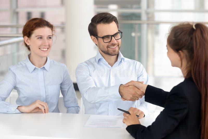 Lycklig ung parunderteckning intecknar mäklaren för handskakningen för försäkringinvesteringavtalet royaltyfria foton