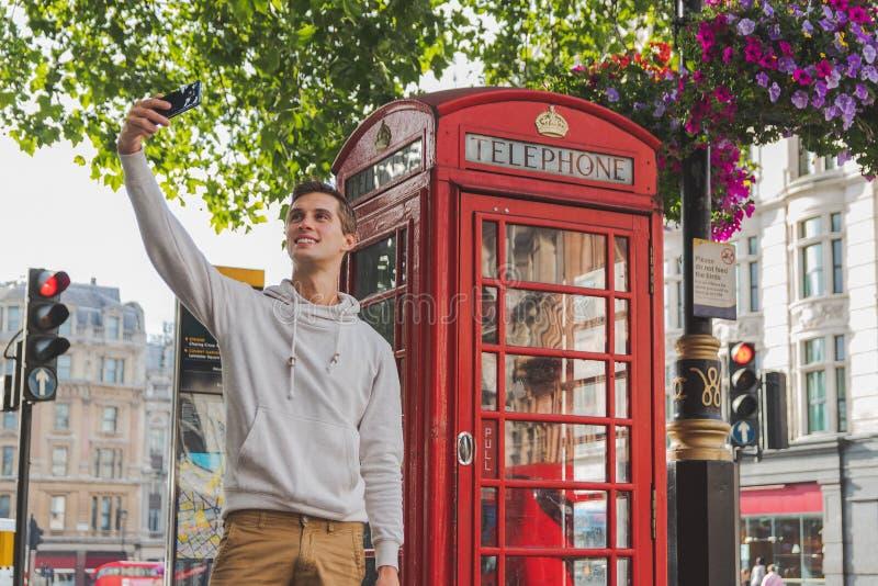 Lycklig ung pojke som framme tar en selfie av en telefonask i Londond arkivbilder