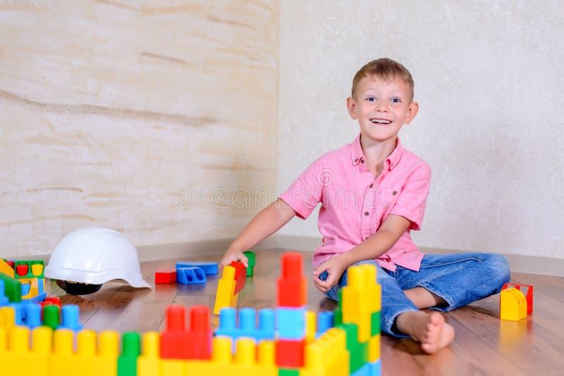 Lycklig ung pojke som spelar med hans byggnadskvarter arkivbilder