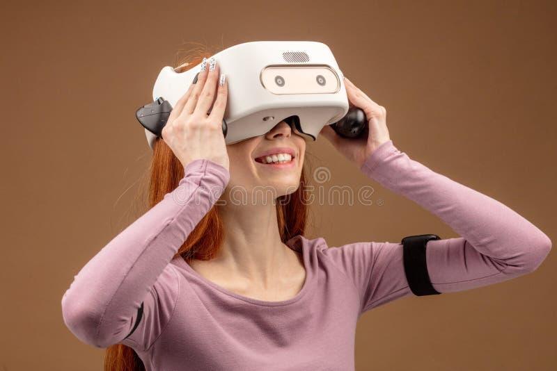 Lycklig ung rödhårig kvinna som använder en virtuell verklighethörlurar med mikrofon royaltyfri bild