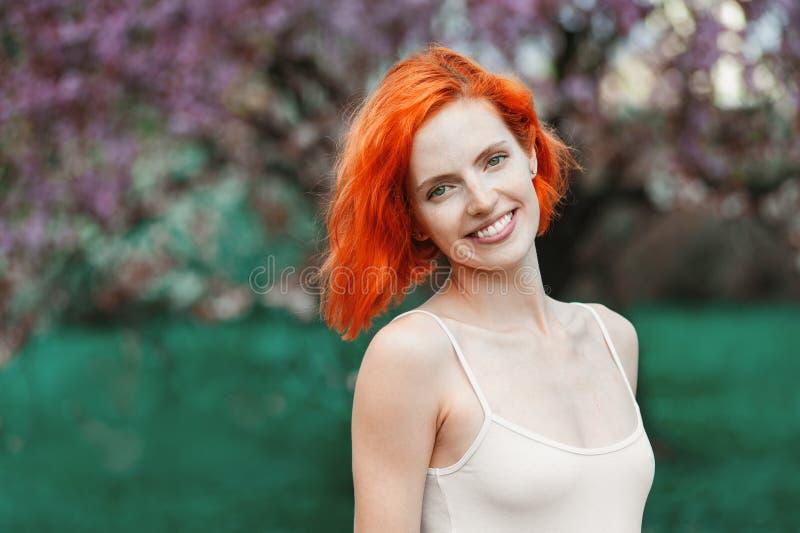 Lycklig ung r?dh?rig kvinna som ser kameran och utomhus st?r p? naturen arkivfoton