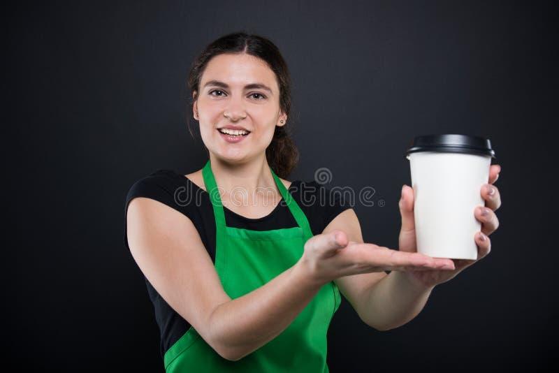 Lycklig ung säljare som erbjuder ett disponibelt kaffe royaltyfria foton
