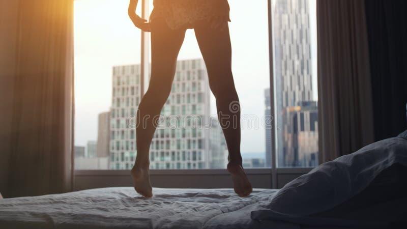 Lycklig ung sexig kvinnabanhoppning på säng i lyxig lägenhet på solnedgångtid förlora upp royaltyfria foton