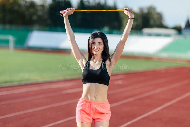 Lycklig ung sportbrunettkvinna i sportswearen som poserar med det gula överhopprepet på stadioninstagramstilen Sund aktiv royaltyfri fotografi