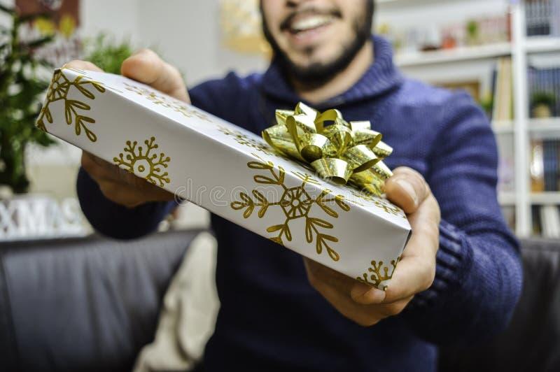 Lycklig ung stilig man som rymmer och ger en gåva till någon arkivbilder