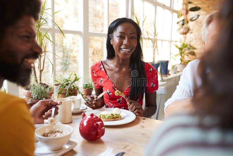 Lycklig ung svart kvinna som äter frunch med vänner på ett kafé royaltyfria foton