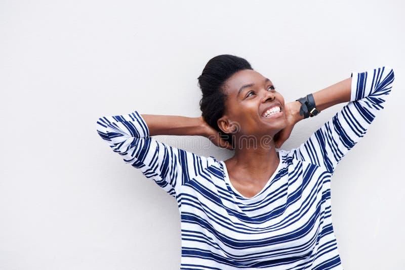 Lycklig ung svart kvinna som ler med händer bak huvudet royaltyfri foto