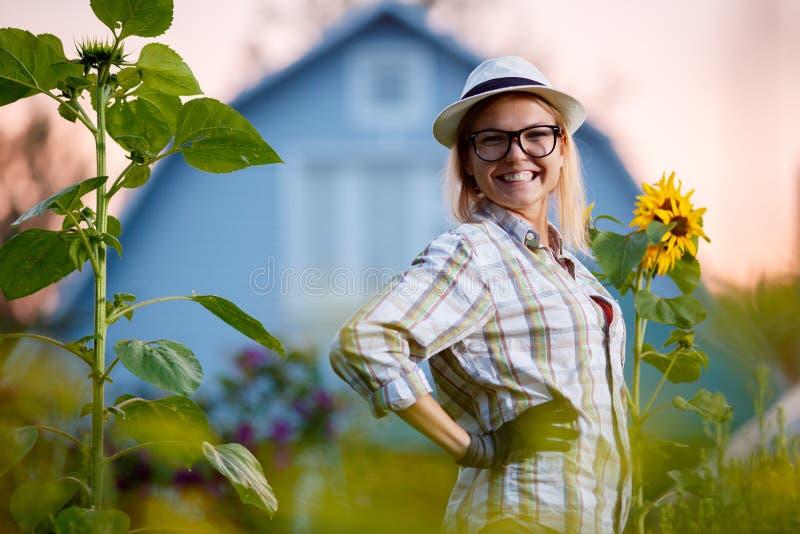 Lycklig ung trädgårdsmästare som poserar i trädgård för hennes stuga royaltyfri bild