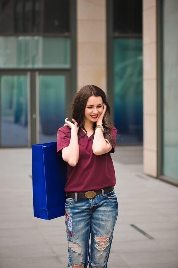 Lycklig ung trendig kvinna med påsar som har ett avbrott, når att ha shoppat royaltyfri foto