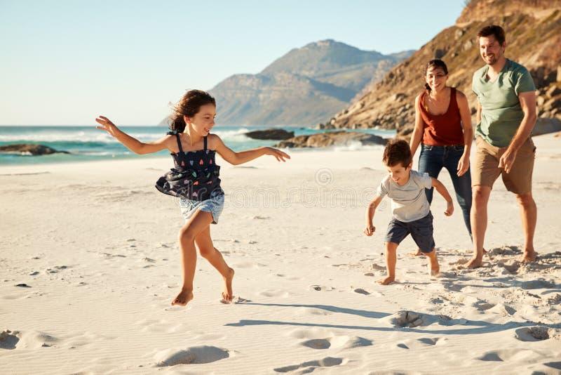 Lycklig ung vit familj på ferie som tillsammans undersöker en strand, full längd royaltyfria foton