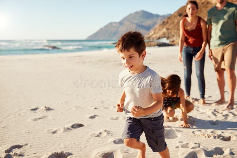 Lycklig ung vit familj på ferie som tillsammans undersöker en strand, full längd, slut upp royaltyfri foto