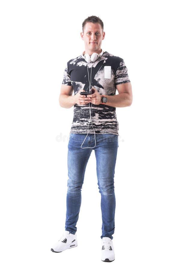 Lycklig ung vuxen man med hörlurar och smartphonen som ler och ser kameran royaltyfri fotografi
