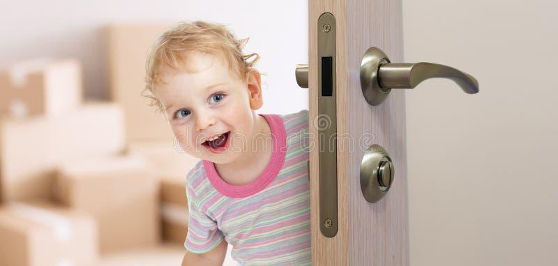 Lycklig unge bak dörr i nytt rum royaltyfri fotografi