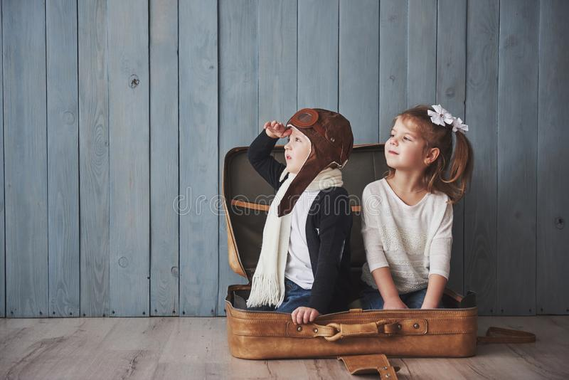 Lycklig unge i pilot- hatt och lilla flickan som spelar med den gamla resväskan Barndom Fantasi fantasi för dublin för bilstadsbe royaltyfria foton