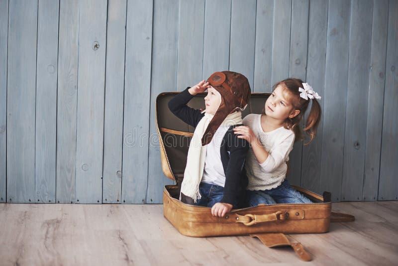 Lycklig unge i pilot- hatt och lilla flickan som spelar med den gamla resväskan Barndom Fantasi fantasi för dublin för bilstadsbe royaltyfria bilder