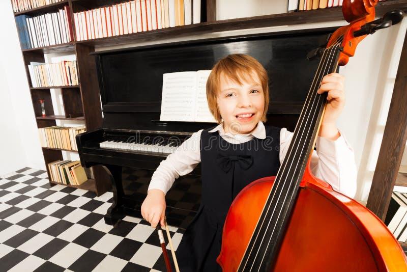 Lycklig unge i skolaklänningen som spelar på violoncellen royaltyfri bild