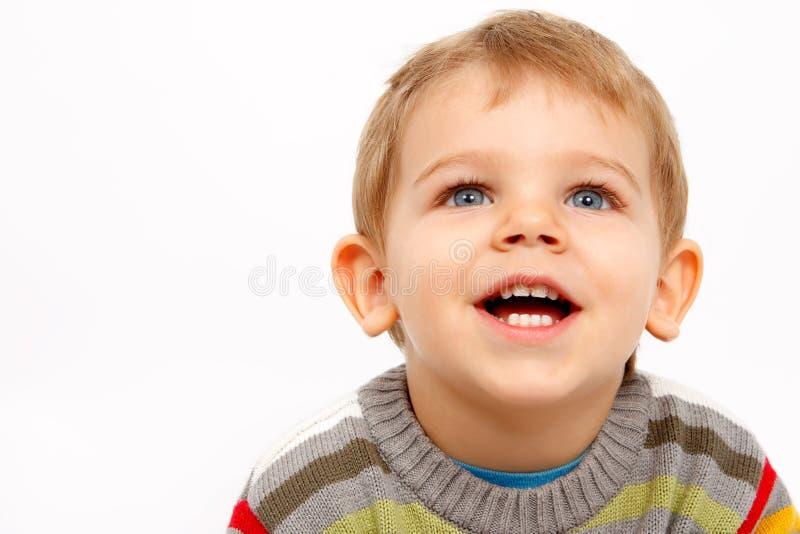 Lycklig unge i vinterkläder som ser upp royaltyfri foto