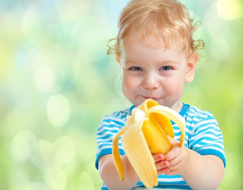 Lycklig unge som äter bananfrukt. sund mat som äter begrepp. fotografering för bildbyråer