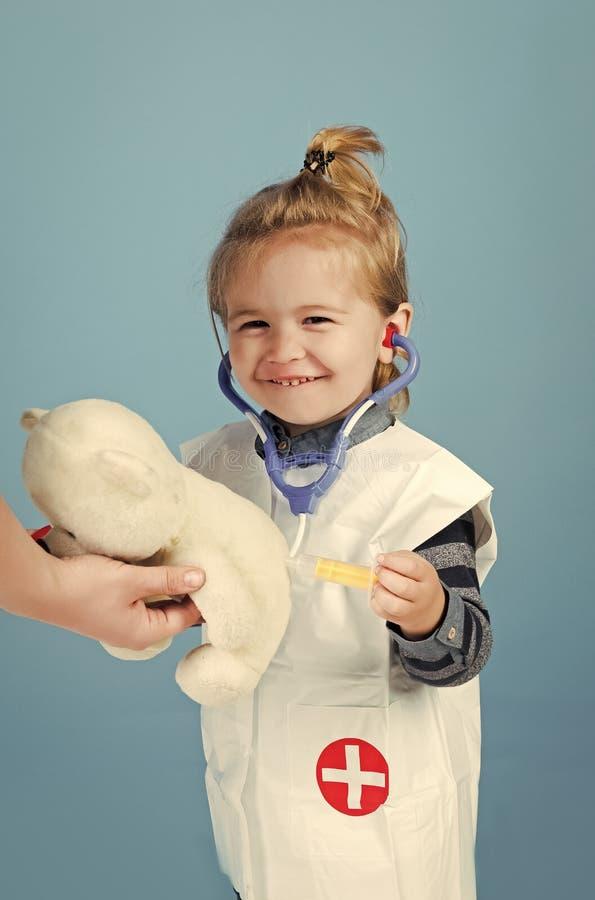 Lycklig unge som har gyckel Den lyckliga ungen med stetoskopet, injektionsspruta gör injektionen till nallebjörnen royaltyfri bild