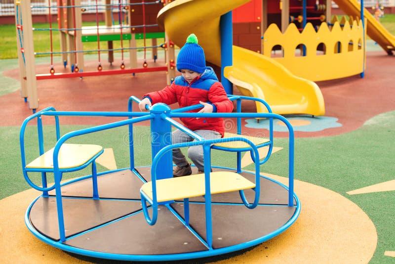 Lycklig unge som har gyckel på den utomhus- lekplatsen Gullig pys som bär varm kläder Roligt barn som utomhus spelar i kall höst fotografering för bildbyråer