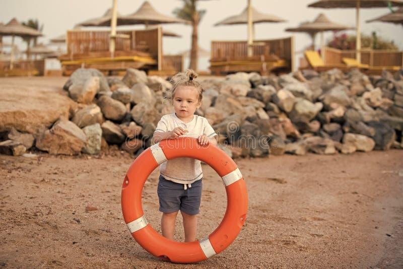 Lycklig unge som har gyckel Pysbarnanseende och hållande livcirkel på stranden arkivbilder