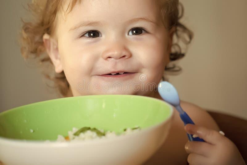 Lycklig unge som har gyckel Stående av att le att äta för barn arkivbild