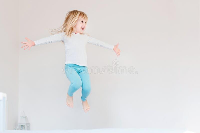 Lycklig unge som hoppar över säng Gullig liten blond flicka som har gyckel inomhus Lyckligt och oförsiktigt barndombegrepp arkivfoto