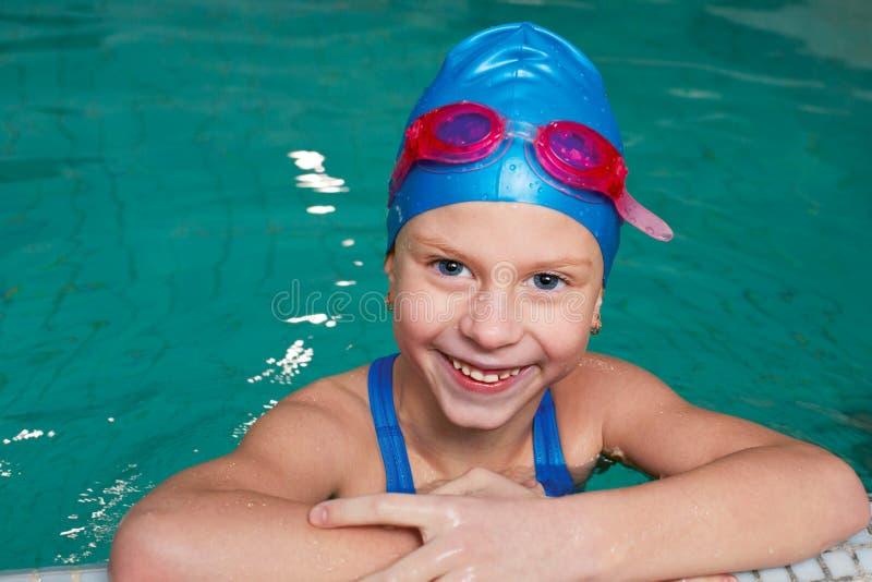 Lycklig unge som skrattar i en simbassäng royaltyfri fotografi