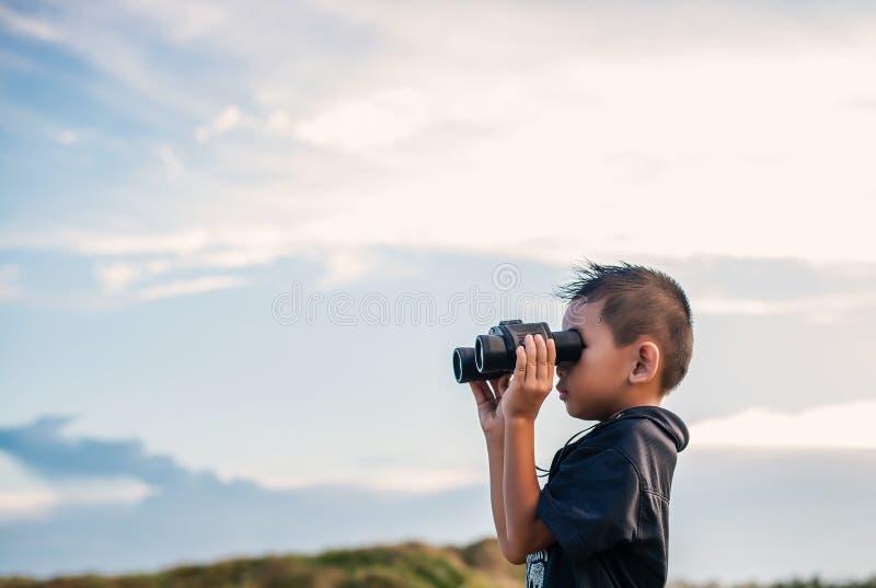 Lycklig unge som spelar kikare i ängarna royaltyfri bild