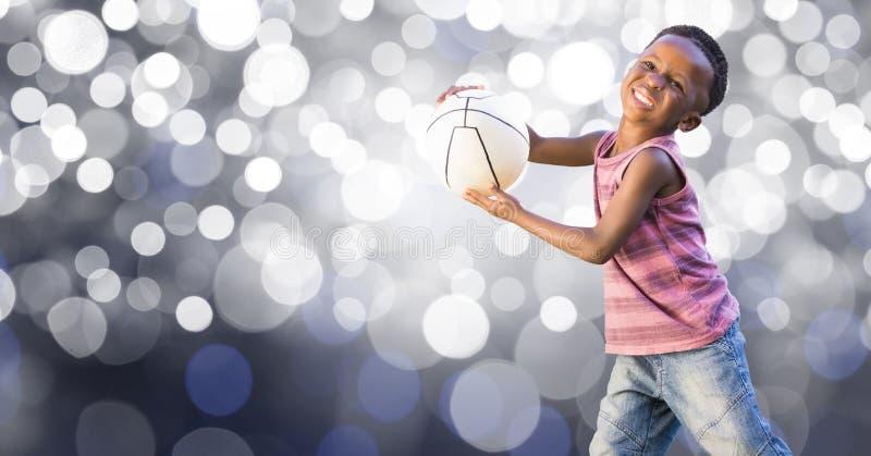 Lycklig unge som spelar med bollen över bokeh arkivfoton