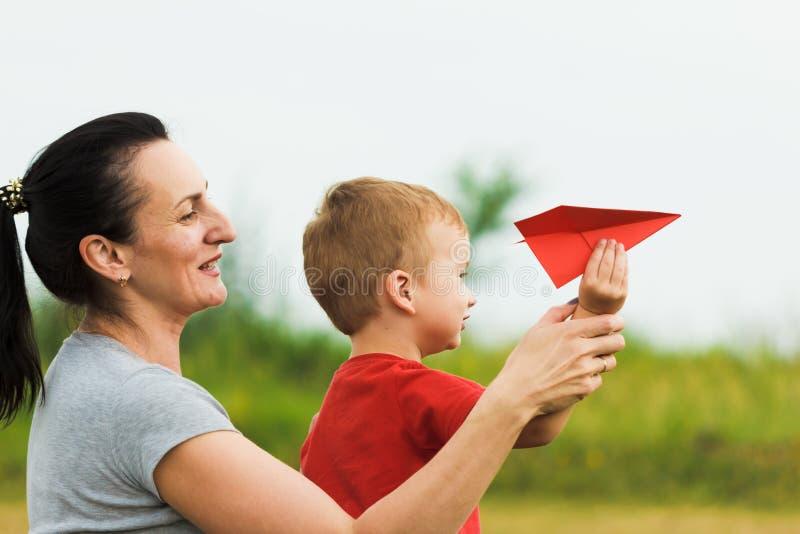 Lycklig unge som spelar med det pappers- flygplanet för moder och för leksak mot sommarhimmel royaltyfria foton