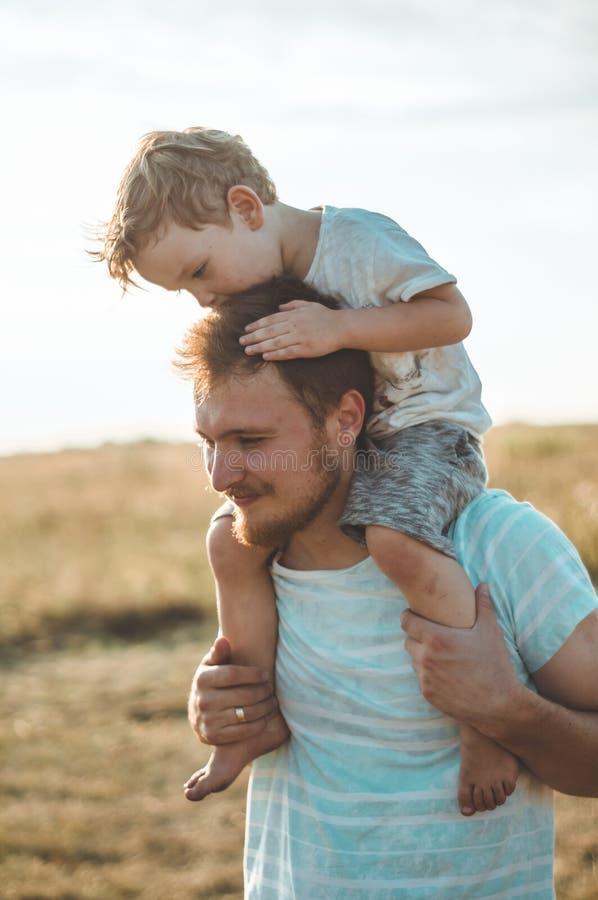 Lycklig unge som spelar med fadern Farsa och son utomhus Bärande barn för fader på hans baksida Lycklig familj i sommarfält fotografering för bildbyråer