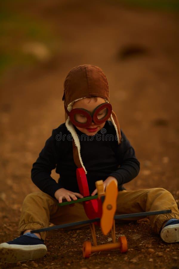 Lycklig unge som spelar med leksakflygplanet arkivbild