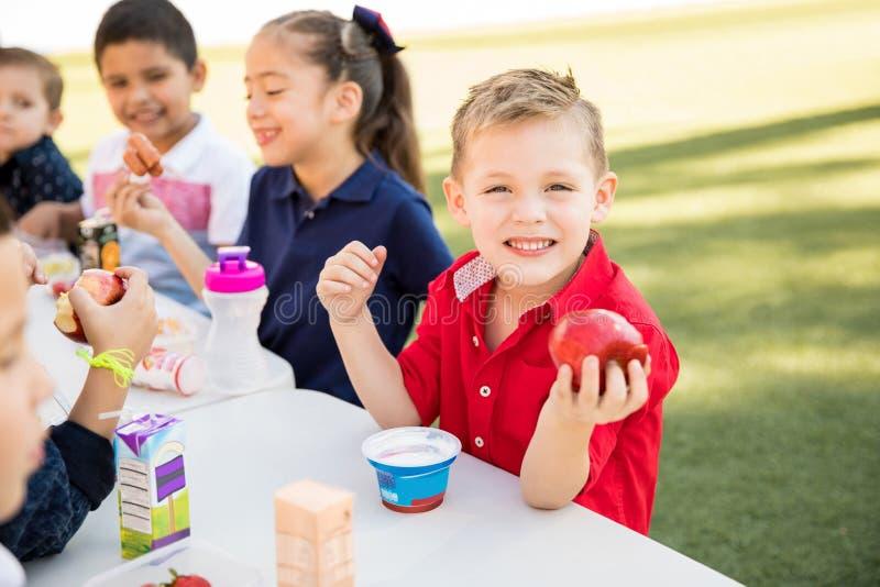 Lycklig unge som tycker om lunchtid på skolan arkivbilder
