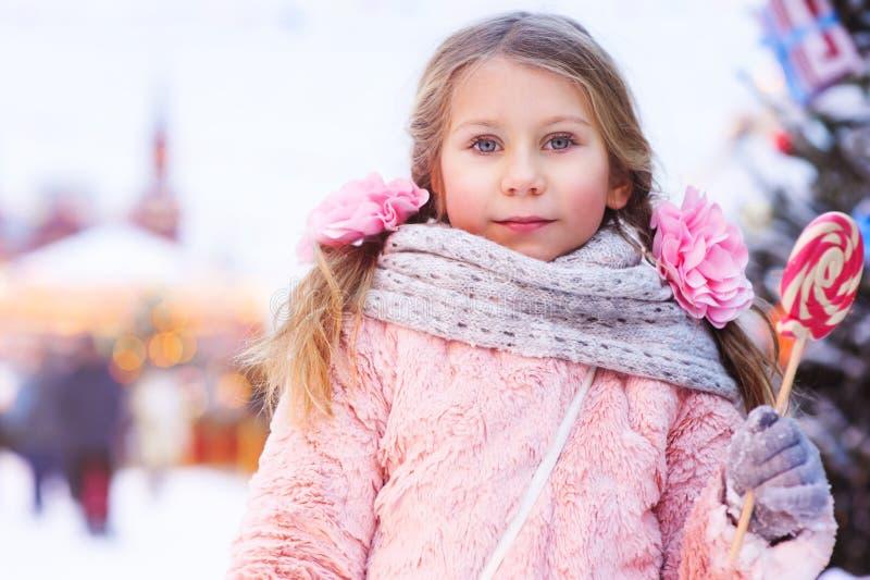 lycklig ungeflicka med julgodisen Stående för vinterferie i aftonMoskvastaden royaltyfri bild