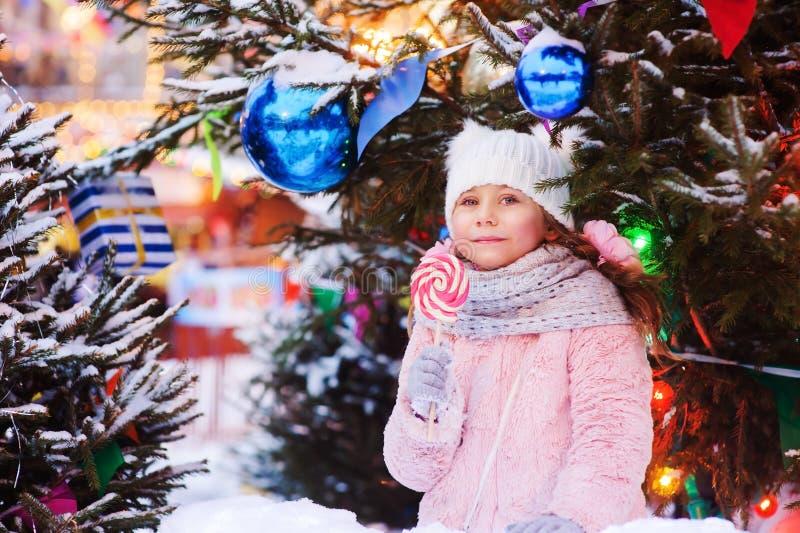 lycklig ungeflicka med julgodisen Ståenden för vinterferie på julträdet dekorerade med leksaker royaltyfri bild