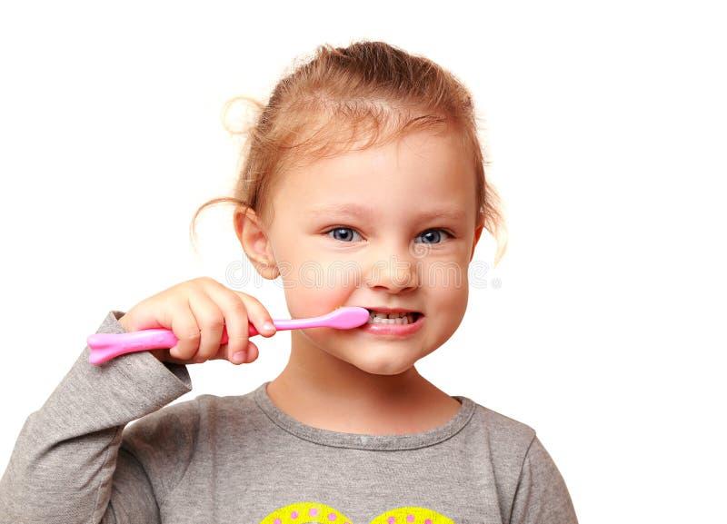 Lycklig ungeflicka som borstar vita tänder arkivfoton