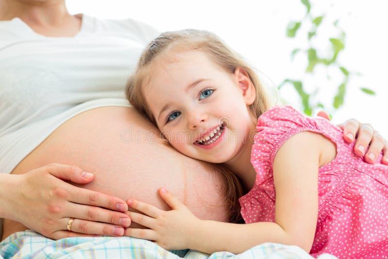 Lycklig ungeflicka som kramar den gravida modern arkivfoto
