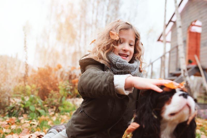Lycklig ungeflicka som spelar med hennes stolta spanielhund för konung charles i höst arkivfoton