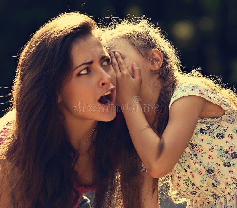 Lycklig ungeflicka som viskar hemligheten till hennes överraskande chockade M royaltyfria bilder