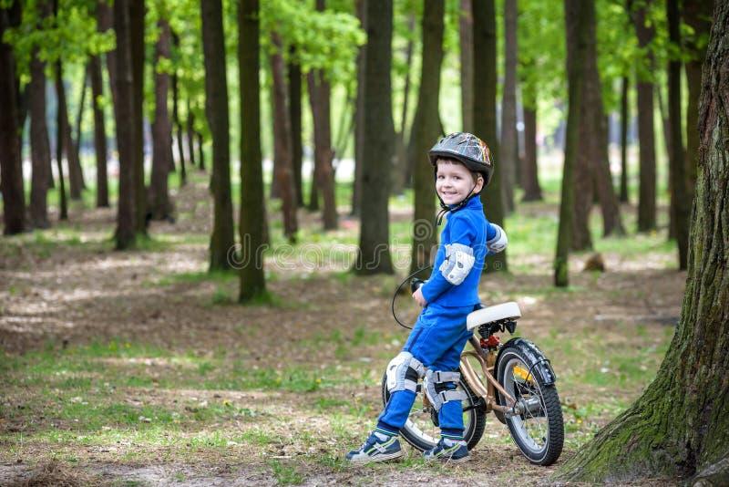 Lycklig ungepojke av 4 år som har gyckel i höst- eller sommarskog med en cykel royaltyfri bild