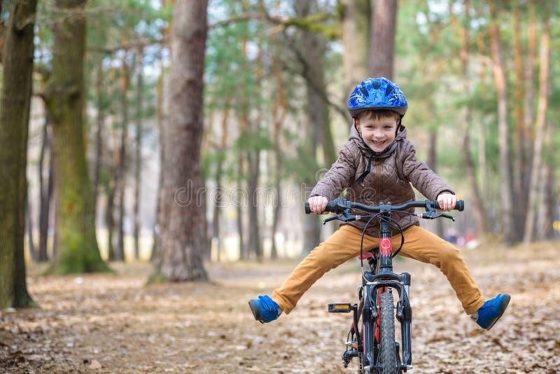 Lycklig ungepojke av 3 eller 5 år som har gyckel i höstskog med en cykel på härlig nedgångdag Bärande cykelhjälm för aktivt barn royaltyfria bilder