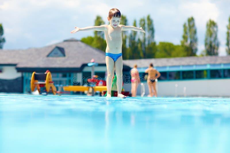 Lycklig ungepojke som är klar att hoppa i pöl fotografering för bildbyråer