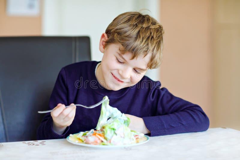 Lycklig ungepojke som äter ny sallad med tomaten, gurkan och olika grönsaker som mål eller mellanmålet Sunt barn som tycker om arkivfoton
